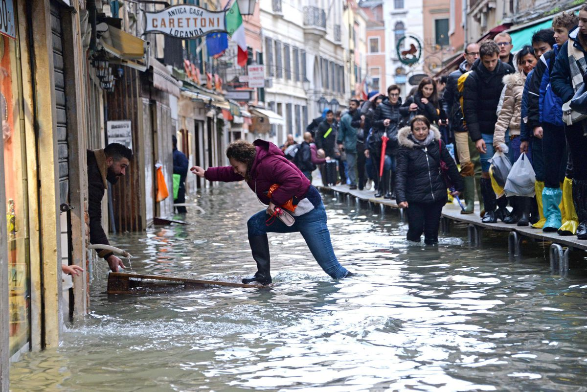 A woman tries to cross a flooded street as people walk on a trestle bridge during high water, in Venice, Italy, on Friday.