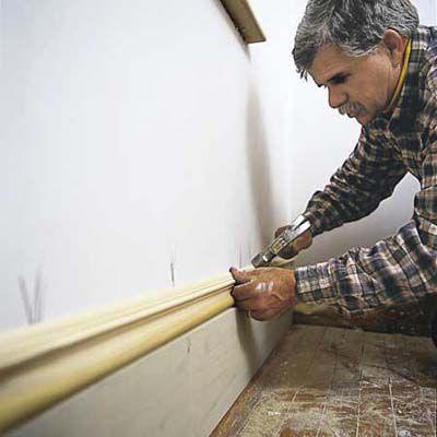 Man Nails On Cap Molding Of Baseboard