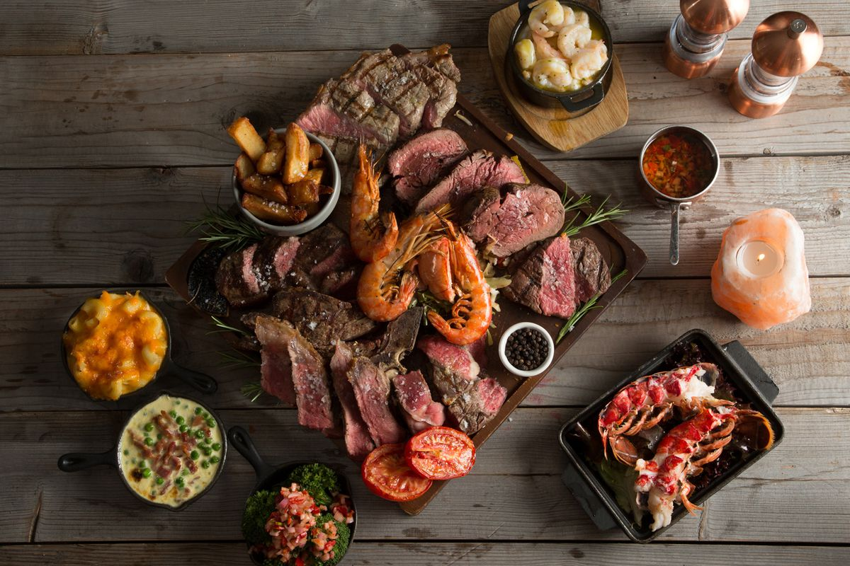A spread of steak, prawns, fries, and lobster from Tomahawk Streakhouse, on a wooden background