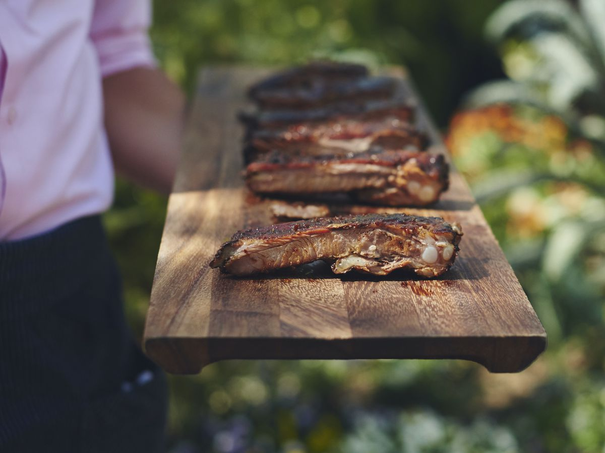 A wooden tray of ribs, cut up and ready to eat.