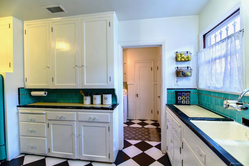 Kitchen with checkerboard floors, white cabinets, and teal tiles.