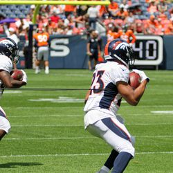 Broncos running backs Devontae Jackson (left) and Devontae Booker move with the ball on a bungee at practice at Broncos Stadium at Mile High.