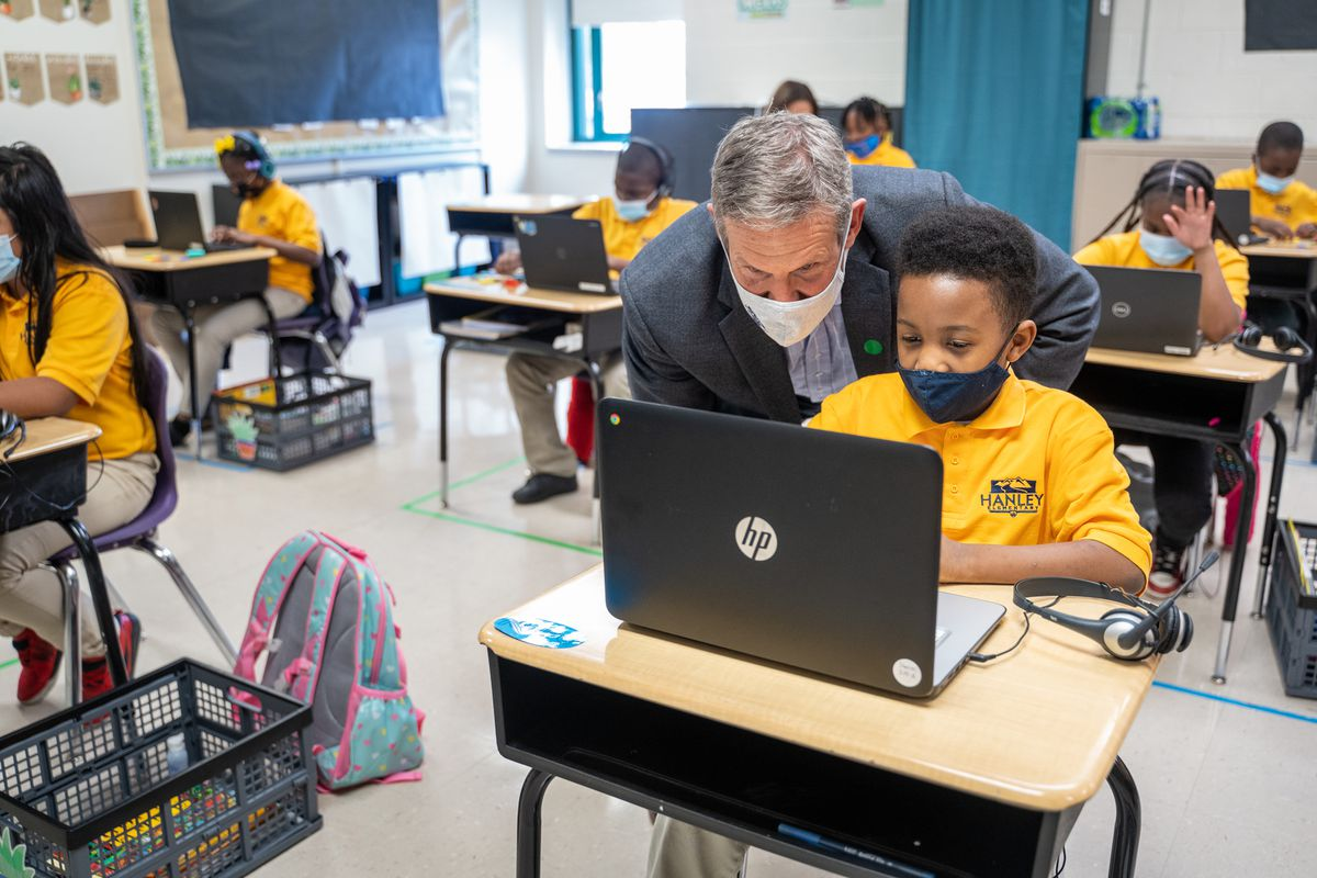 Governor Bill Lee, wearing a mask, looks over a student's shoulder in a classroom, all the students wearing yellow shirts with protective masks.