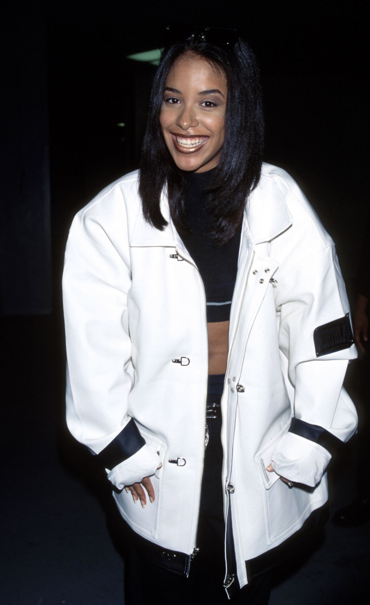 Aaliyah in '90s style oversized clothing.