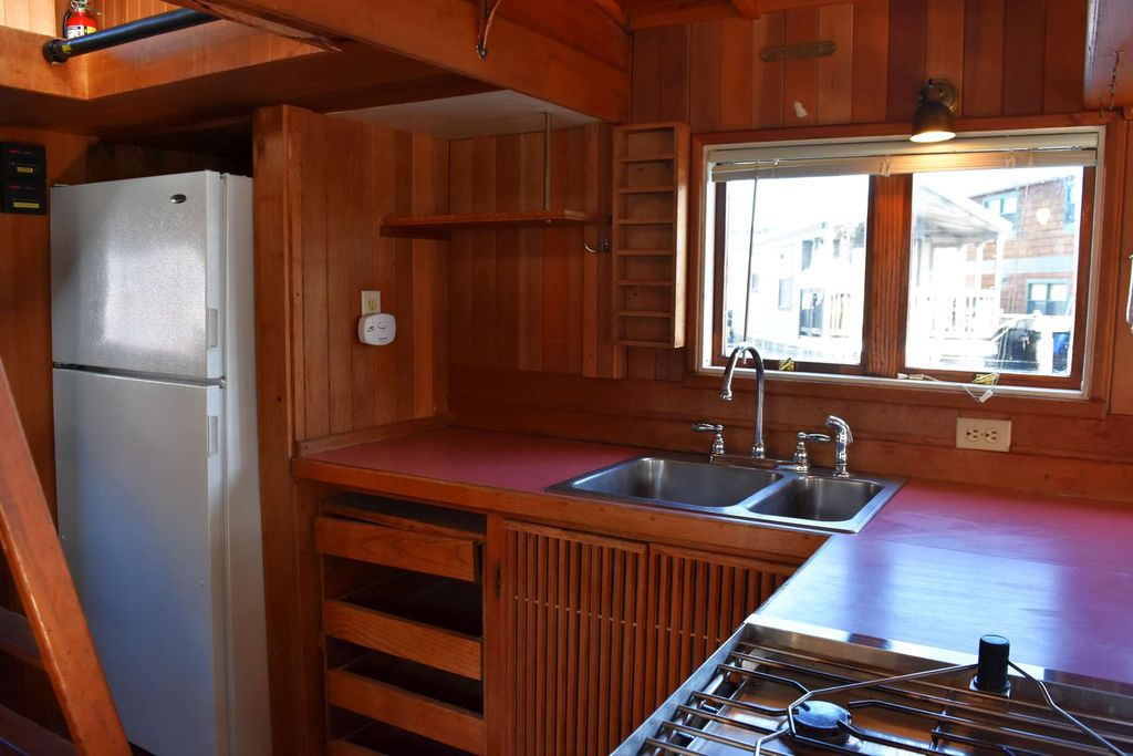 A small kitchen on a boat. A ladder leads up to the bedroom loft.