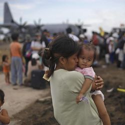 A woman survivor of Typhoon Haiyan weeps as she holds her daughter while waiting for her turn to get on a U.S. Air Force plane to leave for the capital city of Manila, at the airport in Tacloban, central Philippines, Wednesday, Nov. 13, 2013. Typhoon Haiyan, one of the strongest storms on record, slammed into six central Philippine islands on Friday, leaving a wide swath of destruction.
