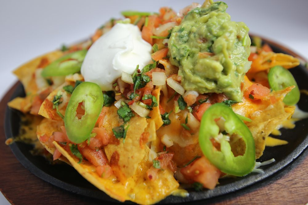 Close-up of tortilla chips covered in melted cheese, jalapeños, and tomatoes, with globs of sour cream and guacamole