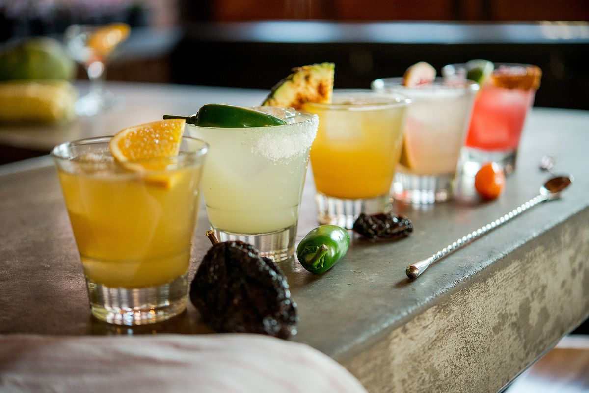 row of colorful drinks with fruit garnishes