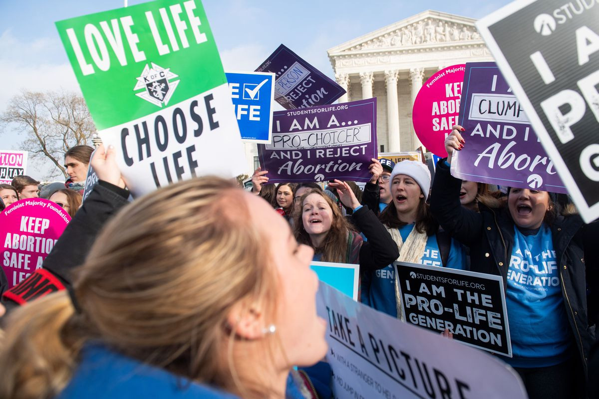 "Anti-abortion activists, including one holding a sign reading ""Love life, choose life,"" as well as abortion-rights activists, demonstrate at the March for Life outside the US Supreme Court in Washington, DC, on January 18, 2019."