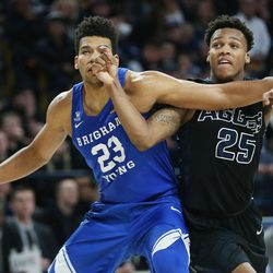 Brigham Young Cougars forward Yoeli Childs (23) and Utah State Aggies forward Dwayne Brown Jr. (25) compete for the repbound in Logan on Saturday, Dec. 2, 2017. BYU won 75-66.