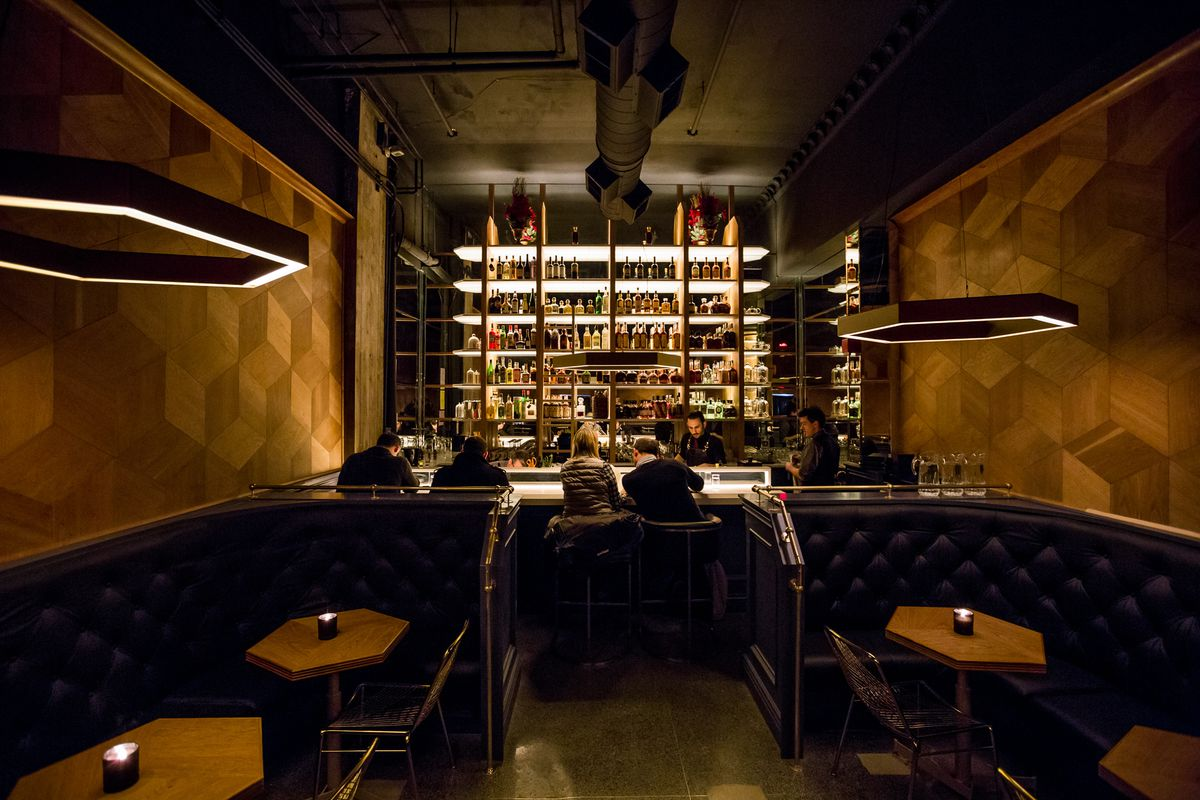 A cocktail bar filled with hexagon shaped lighting, hexagon tables, and a big backlit bar.