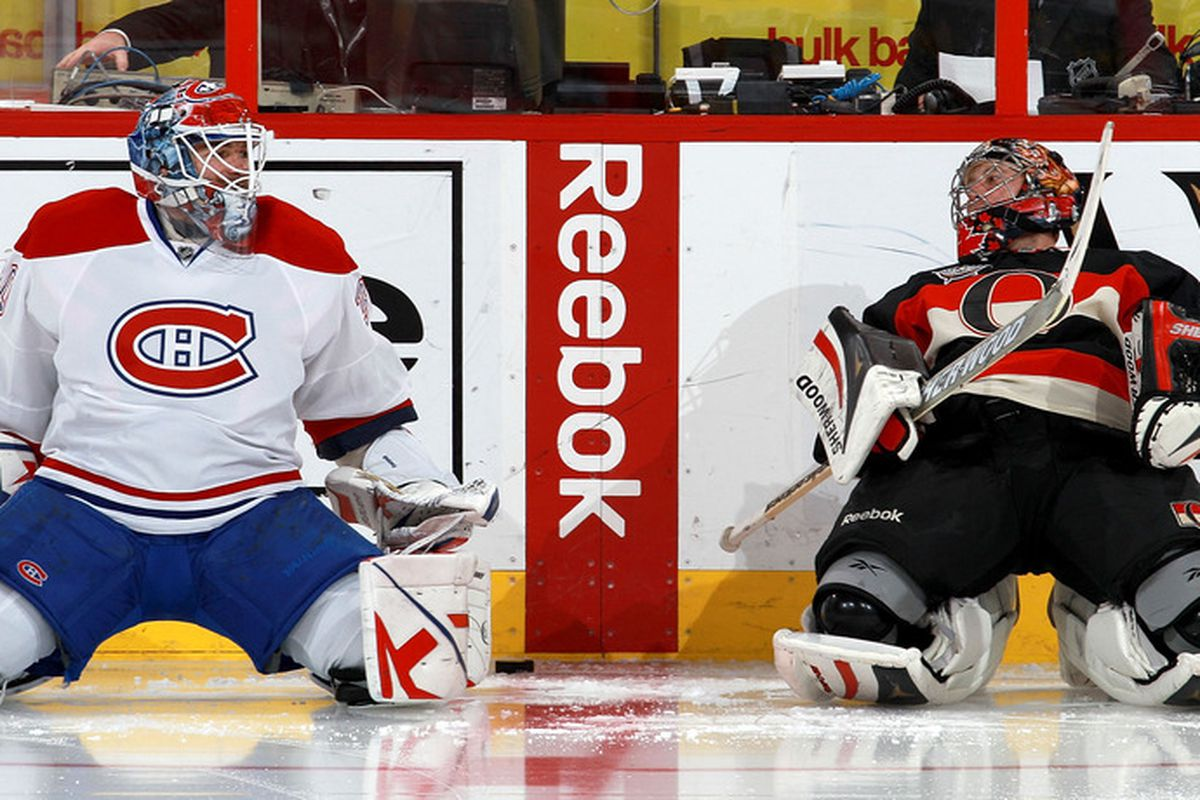 Peter Budaj may have telling Craig Anderson how the Hamilton Bulldogs were sure to beat the Binghamton Senators. Or, they were stretching. (Photo by Jana Chytilova/Freestyle Photography/Getty Images)