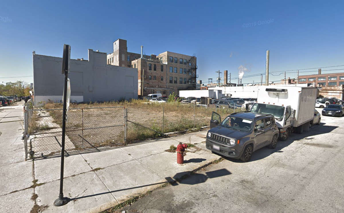 A vacant corner lot surrounded by a chain link fence and concrete sidewalk. There are cars parked in the background and a cluster of mid-rise commercial and loft buildings.