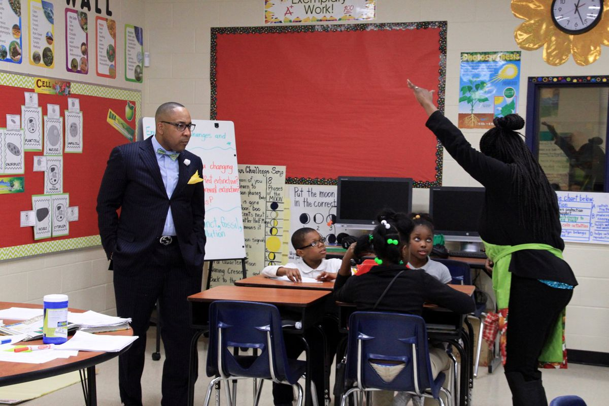Principal Rodney Rowan listens in to a science lesson.