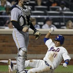 New York Mets shortstop Ruben Tejada scores in front of Pittsburgh Pirates catcher Michael McKenry (55) on Daniel Murphy's third-inning single in their baseball game at Citi Field in New York , Wednesday, Sept. 26, 2012.
