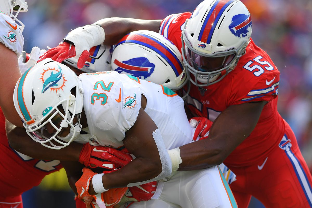 Miami Dolphins running back Kenyan Drake runs with the ball as Buffalo Bills defensive end Jerry Hughes defends during the third quarter at New Era Field.