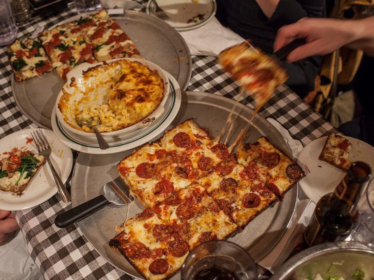 a square pepperoni pizza being served onto plates over a black and white checked tablecloth with macaroni and cheese in a dish