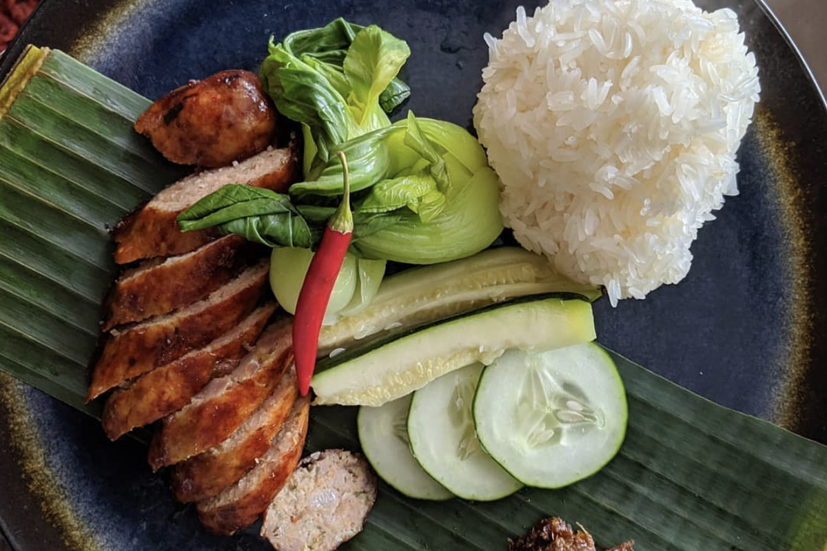 A top-down view of a blue plate with Lao pork sausage, spicy jaew bong, cold steamed vegetables, and sticky rice.