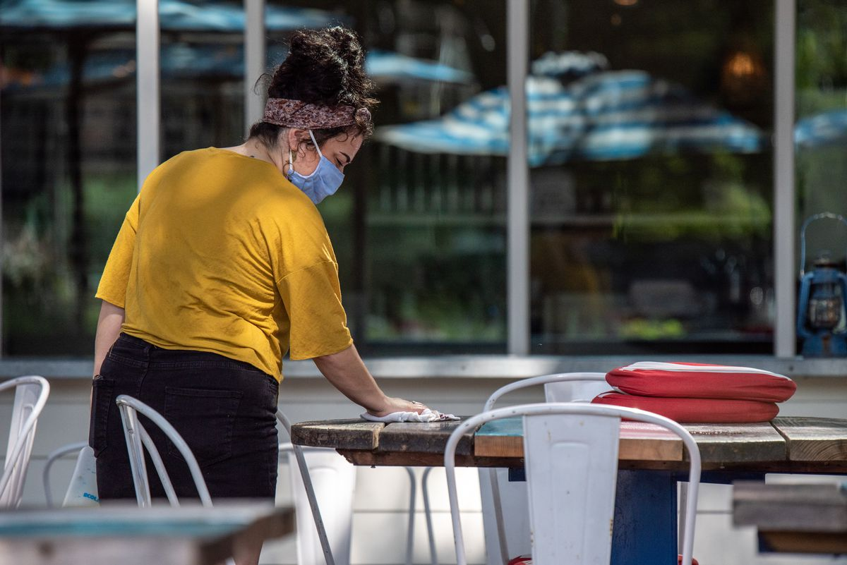 A staffer wiping down tables at Perla's in June
