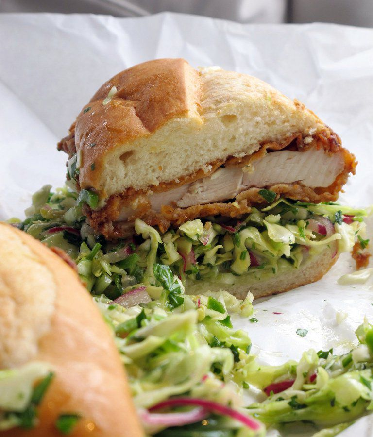 A fried chicken sandwich is cut in half, with lettuce spilling out