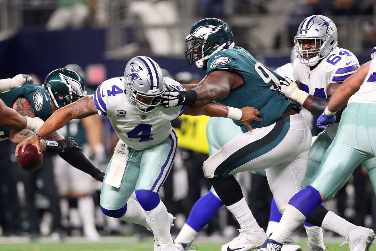 ARLINGTON, TX - NOVEMBER 19:  Dak Prescott #4 of the Dallas Cowboys gets his facemask grabbed by Fletcher Cox #91 of the Philadelphia Eagles in the fourth quarter of a football game at AT&T Stadium on November 19, 2017 in Arlington, Texas.  (Photo by Tom Pennington/Getty Images)