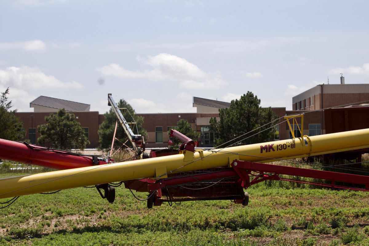Farm equipment sit outside the Otis school, which is sandwiched between a Baptist church and a wheat farm. (Photo by Nic Garcia/Chalkbeat)