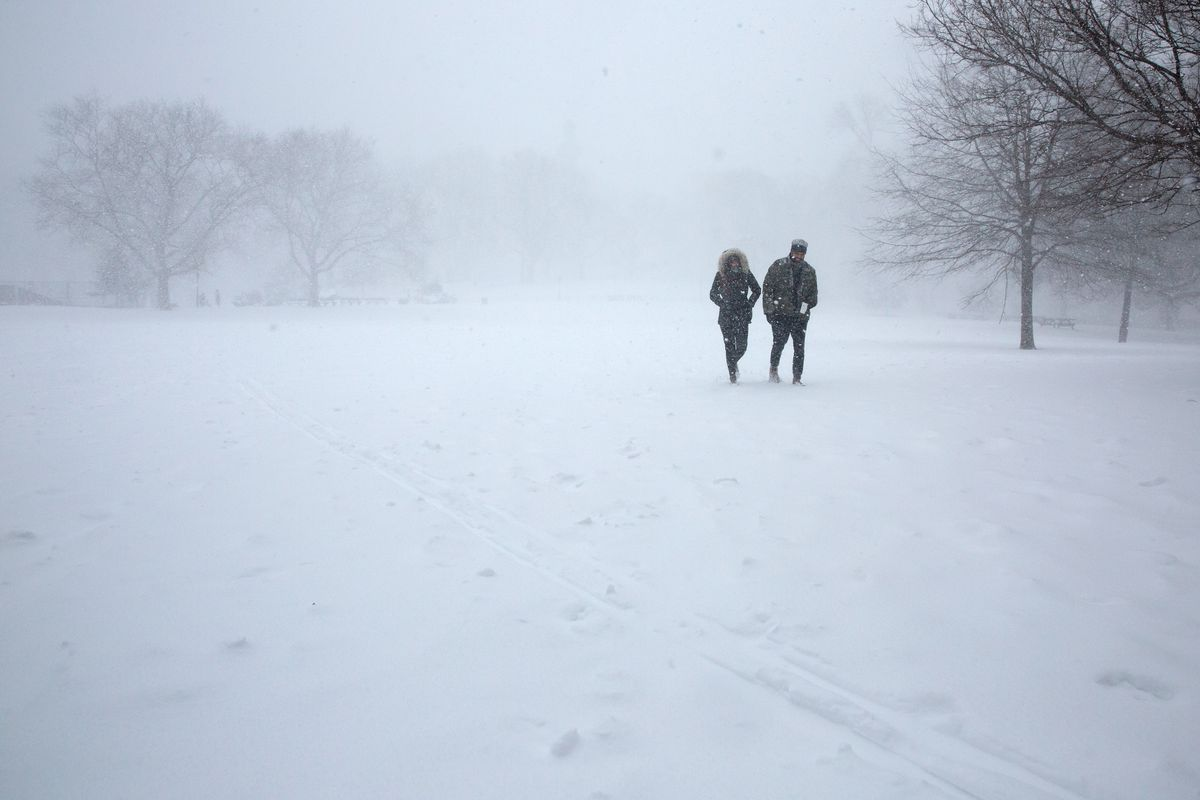 A couple takes a stroll during a blizzard, Feb. 1, 2021.