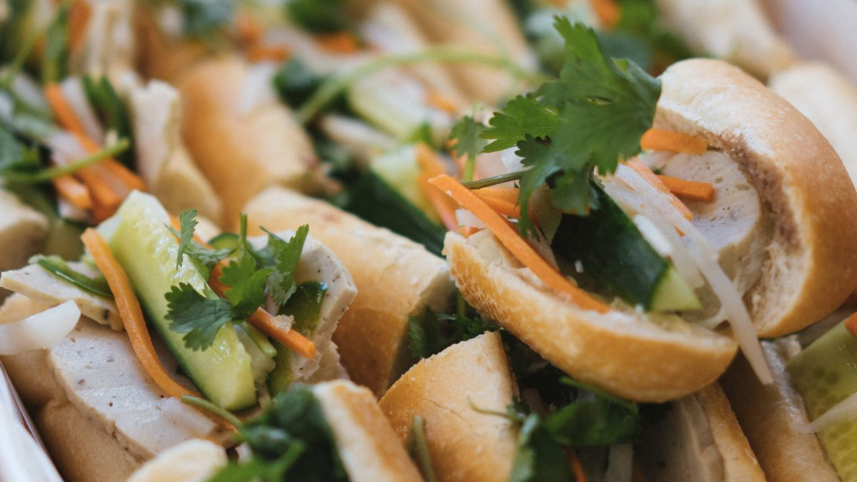 Several banh mi with cilantro, carrots, and cha lua sausage all stacked on top of each other.