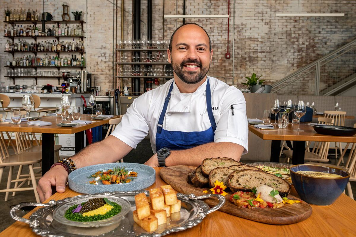 Chef Matt Baker poses for a portrait with dishes from Michele's