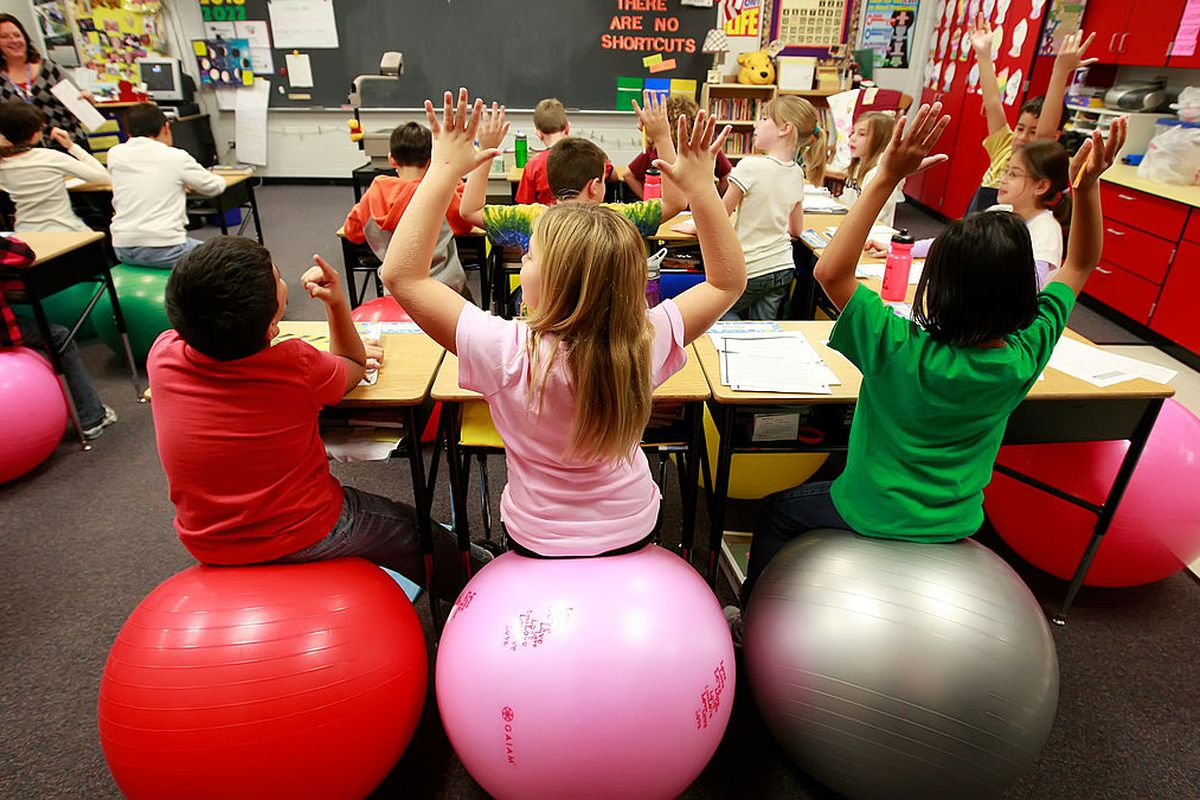 Leela Herena, from right, Emma Miller and Cesar Mendez sit on exercise balls which are used as chairs in a fourth-grade classroom at Creekside Elementary School in Elgin, Illinois, on October 26, 2009.  (Photo by Stacey Wescott/Chicago Tribune/MCT via Getty Images)