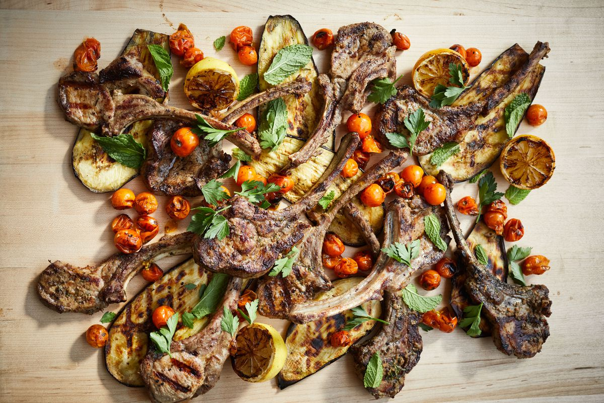 Several bone-in hog chops spread out on a light beige surface with long slices of roasted eggplant, roasted tomatoes, halved roasted lemons, leafy green herbs
