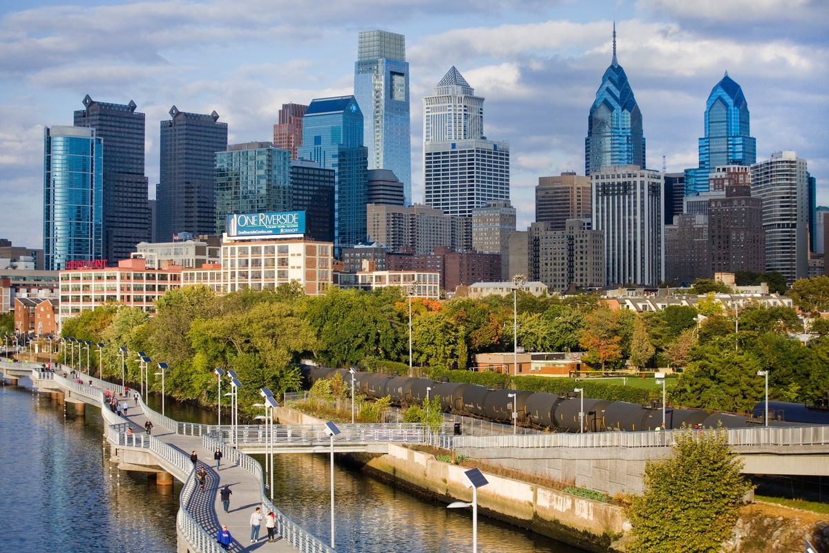 An aerial view of the cityscape of Philadelphia. There is a skyline in the distance with various tall city buildings. There is a river and trees in the foreground.
