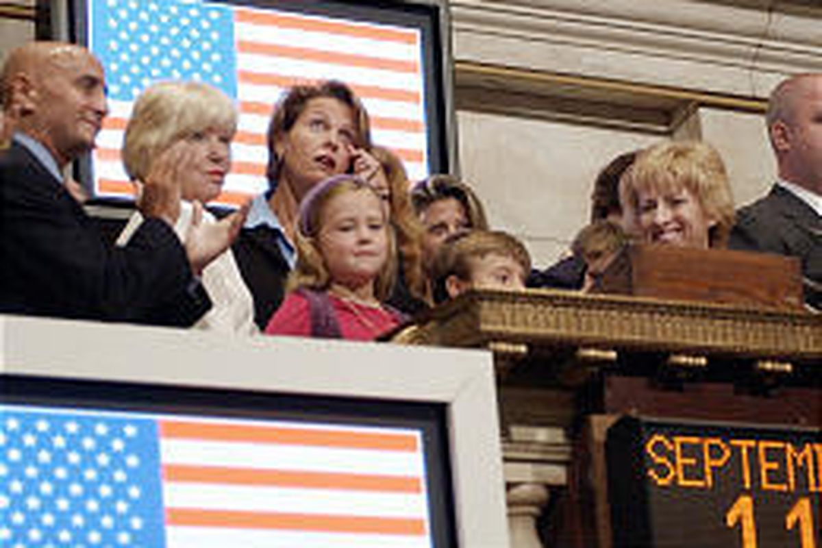 New York Stock Exchange Chairman Dick Grasso, left, applauds opening bell ceremonies Thursday, the second anniversary of the World Trade Center attacks. With Grasso are, from left, Patricia Sutcliffe, mother of Thomas Sutcliffe who died in the attacks, hi