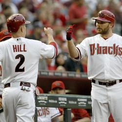 Arizona Diamondbacks' Aaron Hill (2) gets a high-five from teammate Jason Kubel after scoring a run against the Philadelphia Phillies during the first inning of a baseball game Monday, April 23, 2012, in Phoenix.