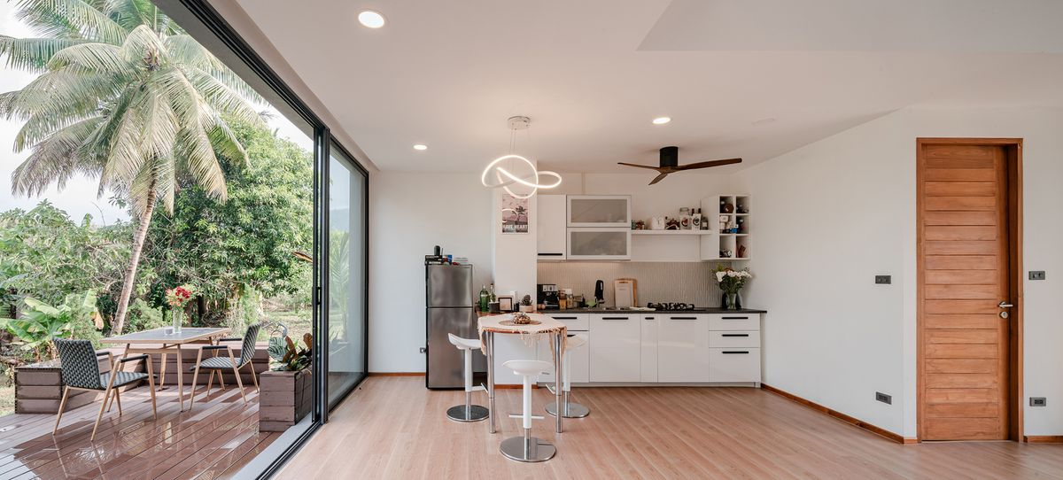Open kitchen with white cabinets and glass walls opening up to outdoor dining area.