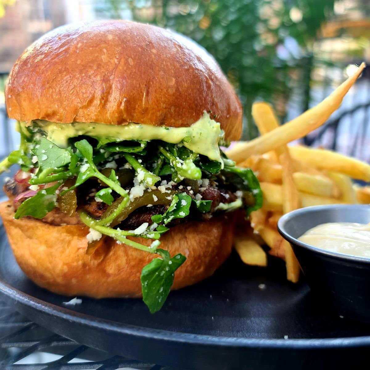 A burger with lots of watercress on a plate with fries