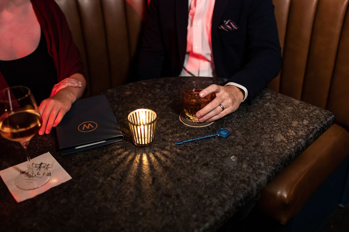 A man and a woman sit side by side at a dimly lit booth with a bar menu booklet, a glass of wine, a brown cocktail, and a tea candle in a striped gold glass.