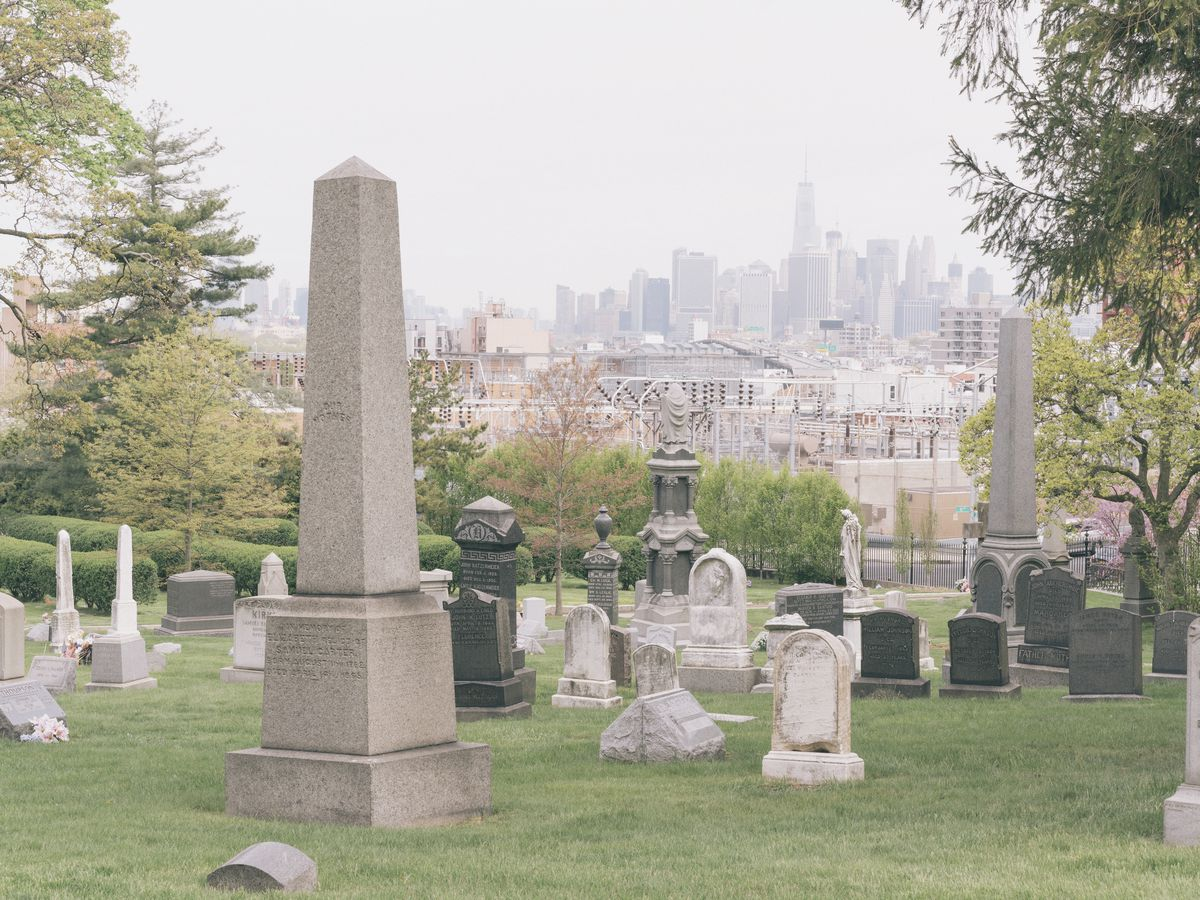 Greenwood cemetery in New York City. There are multiple varied tombstones and trees in the foreground. In the distance are the tall city buildings of the New York City skyline.