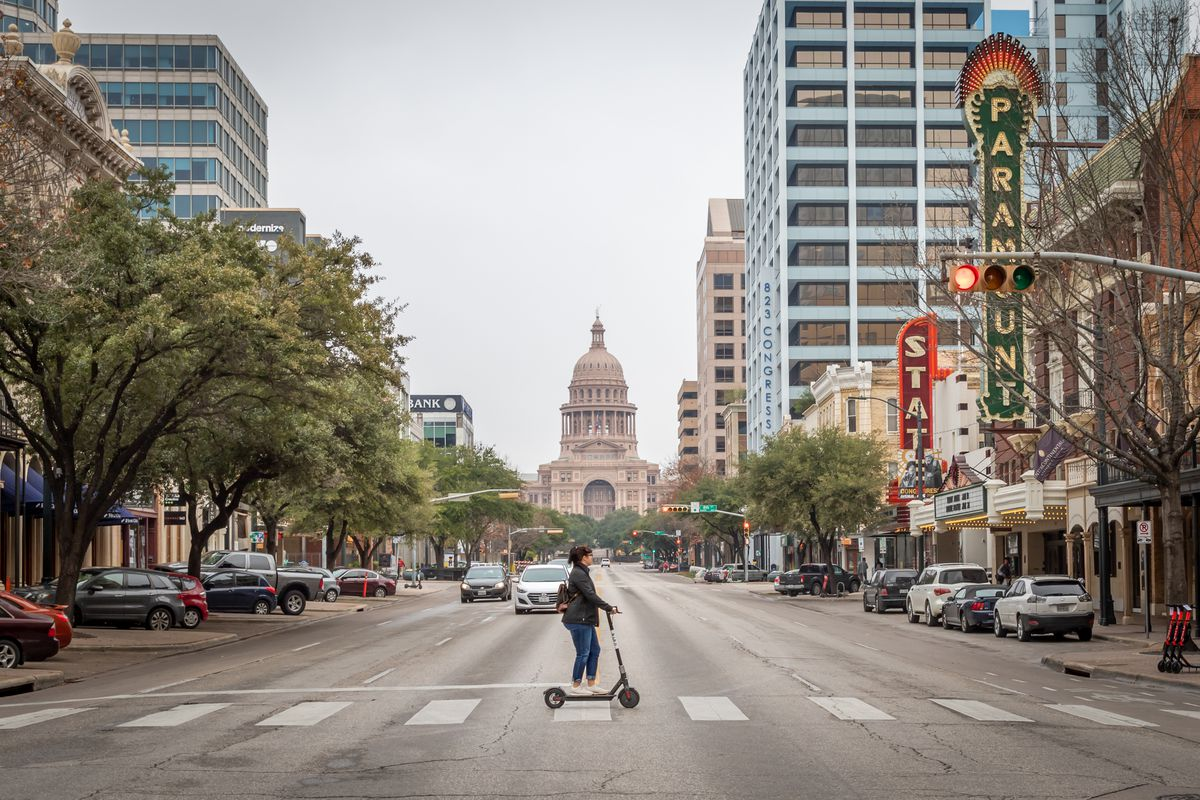 A lone scooter rider travels across a wide city street with cars parked by curbs but not only two driving, on the left lanes of the street. Medium-height office buildings and shorter brick buildings line the street. Vintage theater blades reading Paramount and State extend from buildings on the right. The street leads to a domed building, the state Capitol, and grounds in the background.