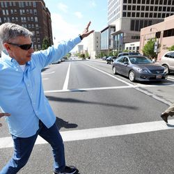 Libertarian presidential candidate Gov. Gary Johnson gestures as he crosses State Street as he and running mate Gov. Bill Weld head out for lunch in Salt Lake City prior to giving a speech at the University of Utah on Saturday, Aug. 6, 2016.