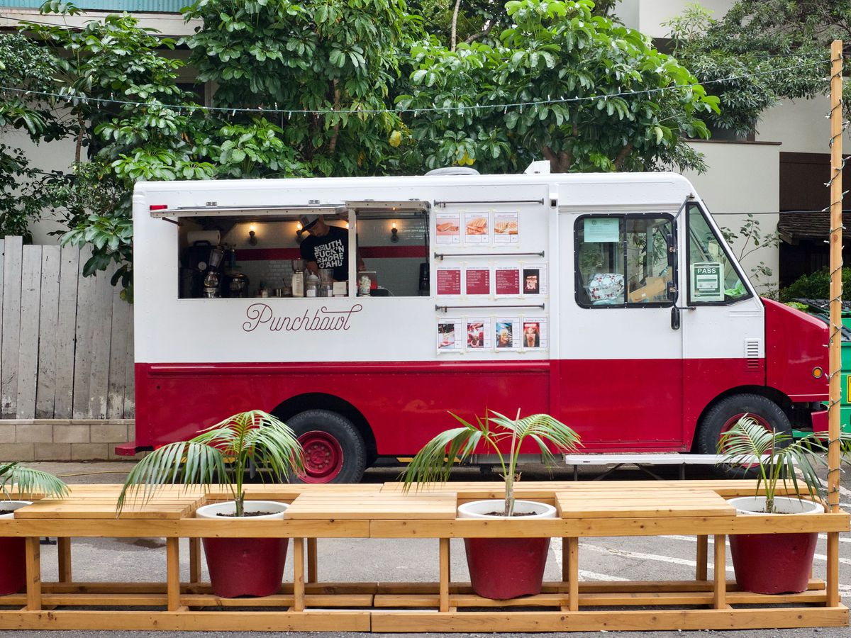 A food truck viewed from inside a cafe, with a long table and seats perched facing out a large window