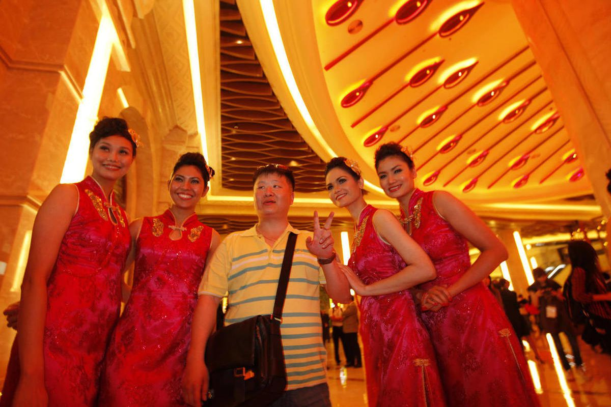 FILE - In this May 15, 2011 file photo, a mainland Chinese visitor is welcomed by hostess at Galaxy Macau as the multibillion-dollar casino resort opened in Macau. Galaxy Entertainment Group plans to double the size of its flagship Macau casino in a $2.1