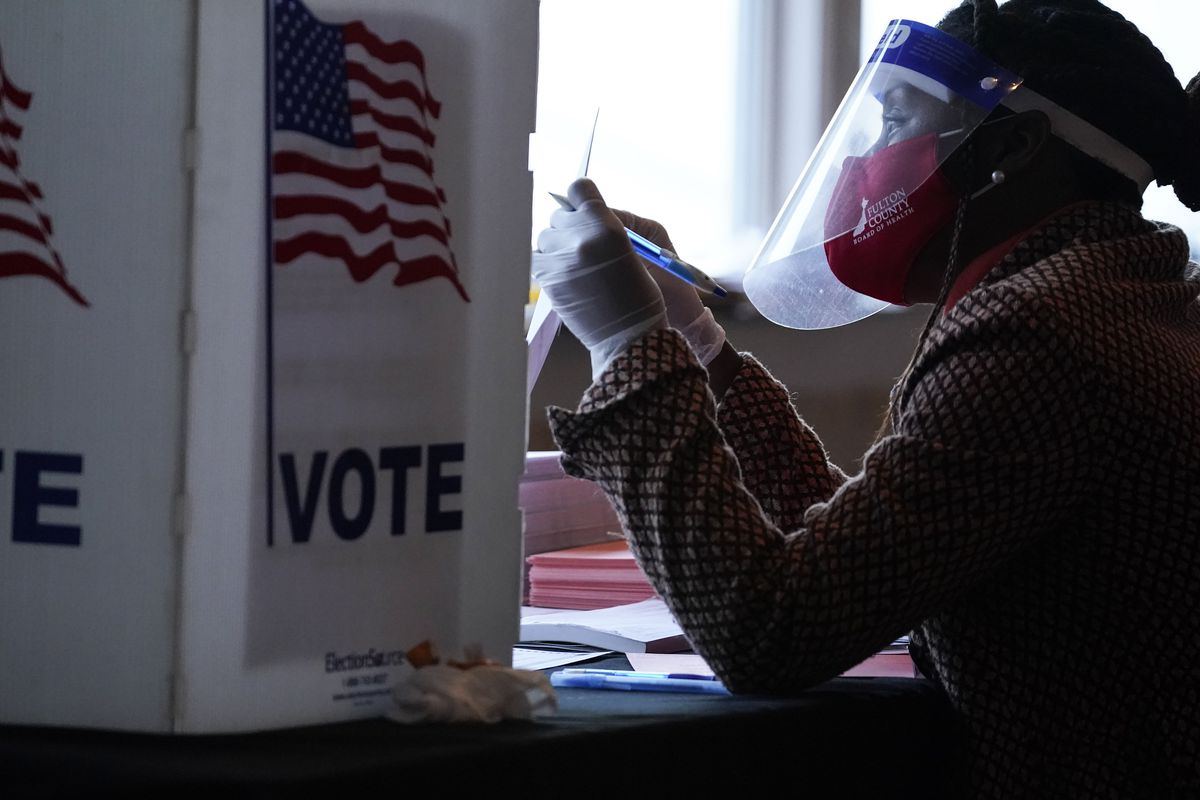 In this Nov. 3, 2020, file photo, a poll worker talks to a voter before they vote on a paper ballot on Election Day in Atlanta.