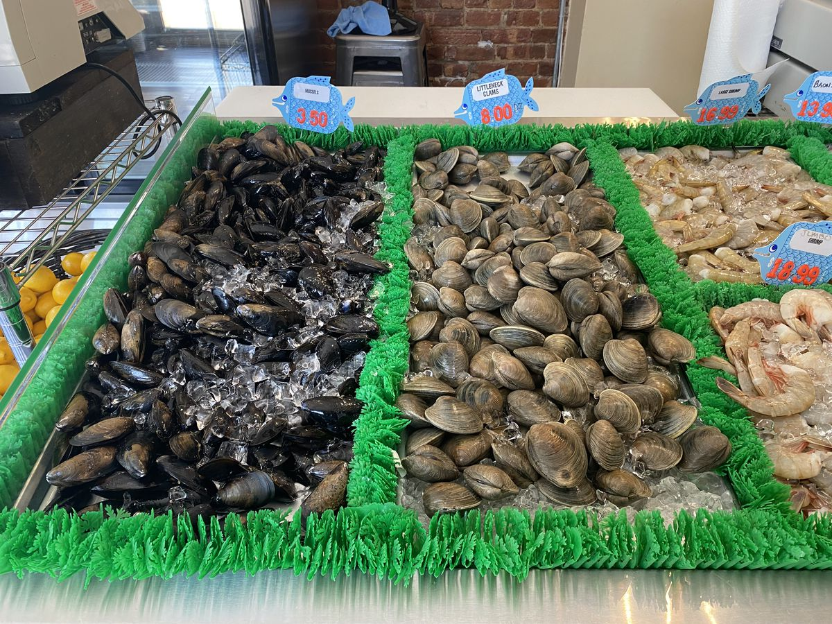 Mussels and clams sit on a bed of ice at a seafood shop advertising fish and bivalves by the pound