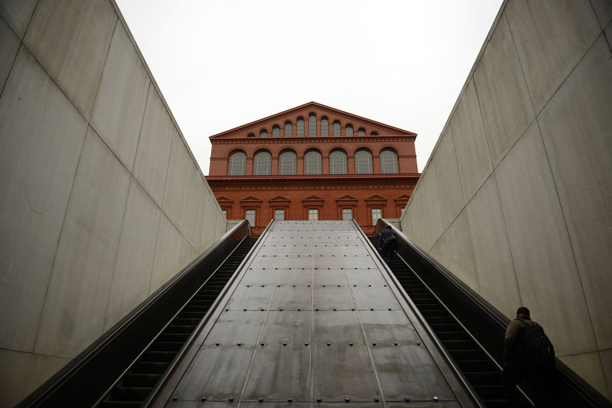 The top of a revival-style building at the top of a subway escalator