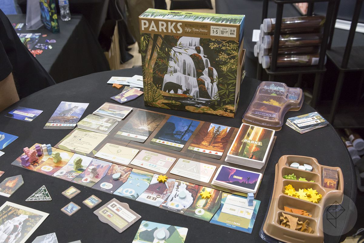 A beauty shot of Parks set up for play. The game includes excellent pack-ins — plastic trays with lids to hold the game pieces, ready to hand out to players once the main box is opened.