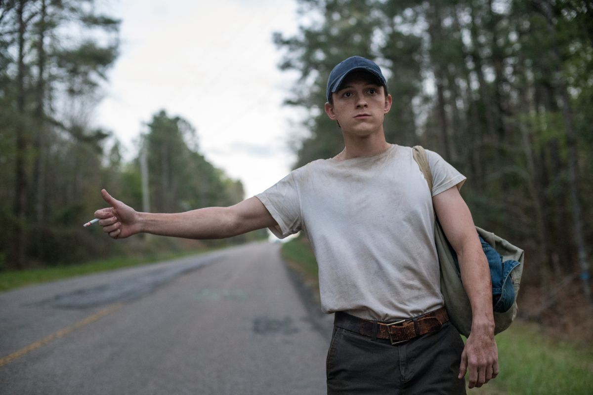 Tom Holland sticks out his thumb to catch a ride as Arvin Russell in The Devil All the Time on Netflix