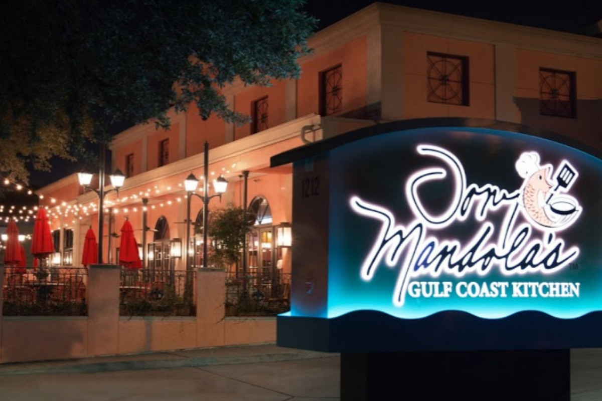 the front of a restaurant at night, with a neon sign reading Tony Mandola's Gulf Coast Kitchen