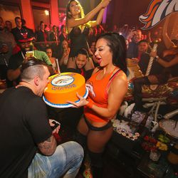 Derek Wolfe takes a bite out of the championship cake at Tao. Photo: Tony Tran
