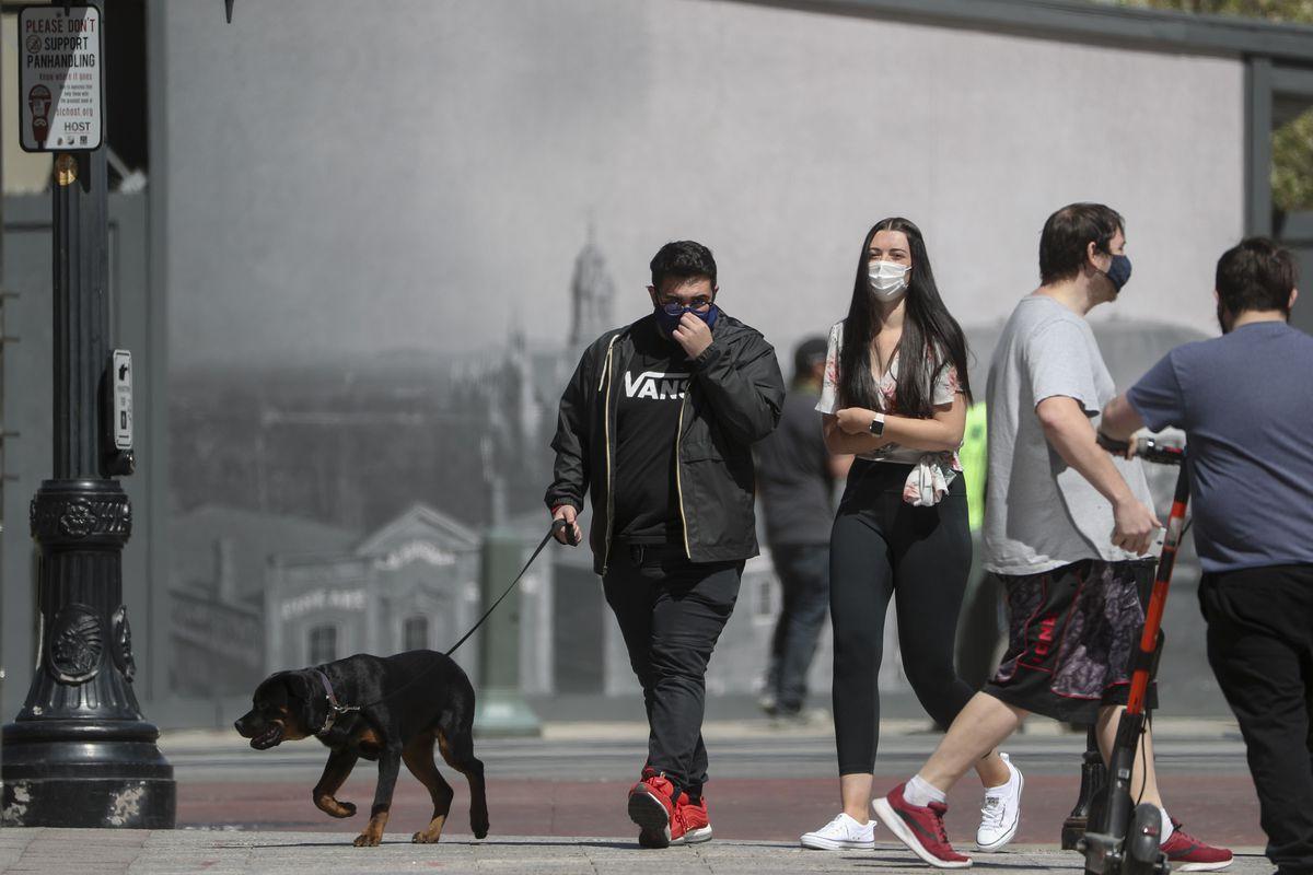 Pedestrians wear masks as they walk on Main Street in Salt Lake City on Friday, April 9, 2021.